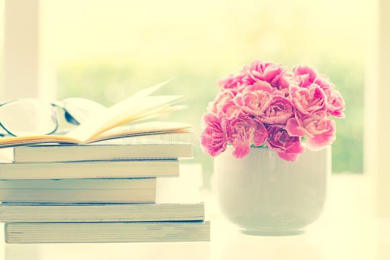 Φρέσκο ρόδινο λουλούδι γαρίφαλων με το υπόβαθρο βιβλίων στοκ εικόνες