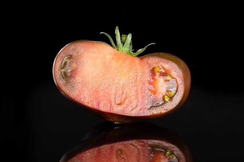 Φρέσκο σκοτεινό primora ντοματών που απομονώνεται στο μαύρο γυαλί στοκ εικόνα με δικαίωμα ελεύθερης χρήσης