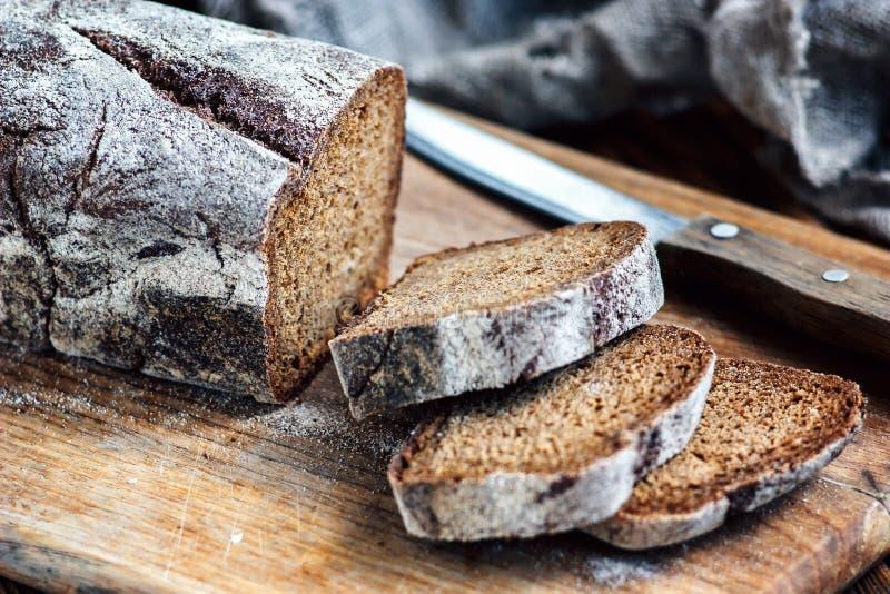 Φρέσκο, σπιτικό ψωμί που τεμαχίζεται με το τέμνον μαχαίρι στον αγροτικό πίνακα, ξύλινο υπόβαθρο στοκ φωτογραφία