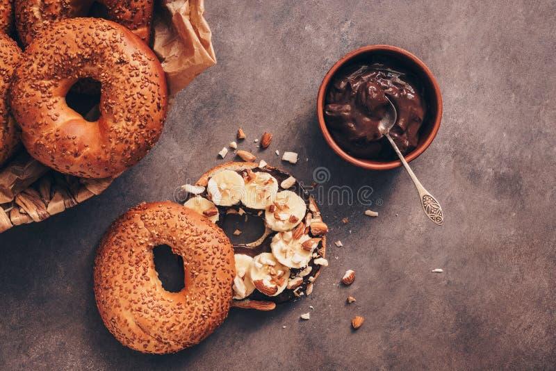 Φρέσκο σπιτικό bagel με την μπανάνα, την κρέμα σοκολάτας και το αμύγδαλο σε ένα σκοτεινό αγροτικό υπόβαθρο r στοκ φωτογραφία με δικαίωμα ελεύθερης χρήσης