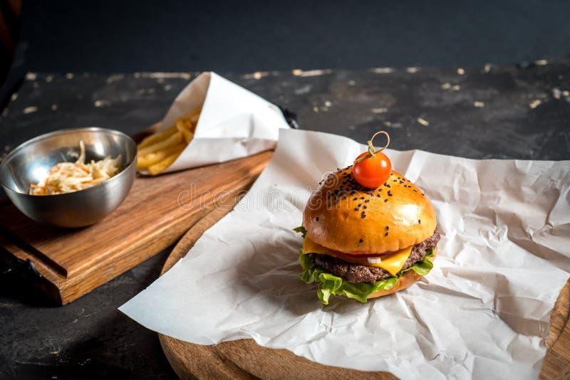 Φρέσκο σπιτικό burger σε λίγο πίνακα κοπής με τις ψημένες στη σχάρα πατάτες, που εξυπηρετούνται με τη σάλτσα κέτσαπ και το άλας θ στοκ εικόνες