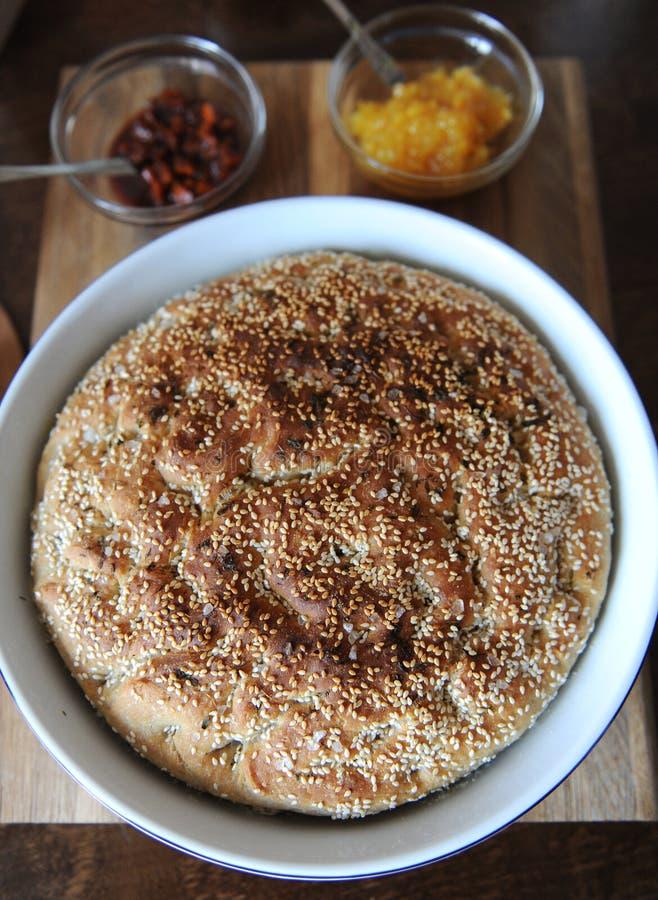 Φρέσκο στρογγυλό ψωμί focaccia με το σουσάμι με κεραμική μορφή Εξυπηρέτηση σε έναν ξύλινο πίνακα Βοτανικό τσάι, φλυτζάνια, μαρμελ στοκ φωτογραφίες με δικαίωμα ελεύθερης χρήσης