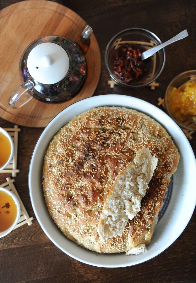 Φρέσκο στρογγυλό ψωμί focaccia με το σουσάμι με κεραμική μορφή Εξυπηρέτηση σε έναν ξύλινο πίνακα Βοτανικό τσάι, φλυτζάνια, μαρμελ στοκ φωτογραφίες