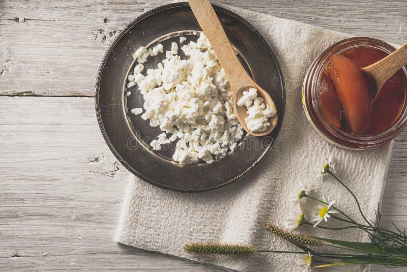 Φρέσκο τυρί εξοχικών σπιτιών με τη μαρμελάδα και λουλούδια στην άσπρη ξύλινη άποψη επιτραπέζιων κορυφών στοκ φωτογραφία
