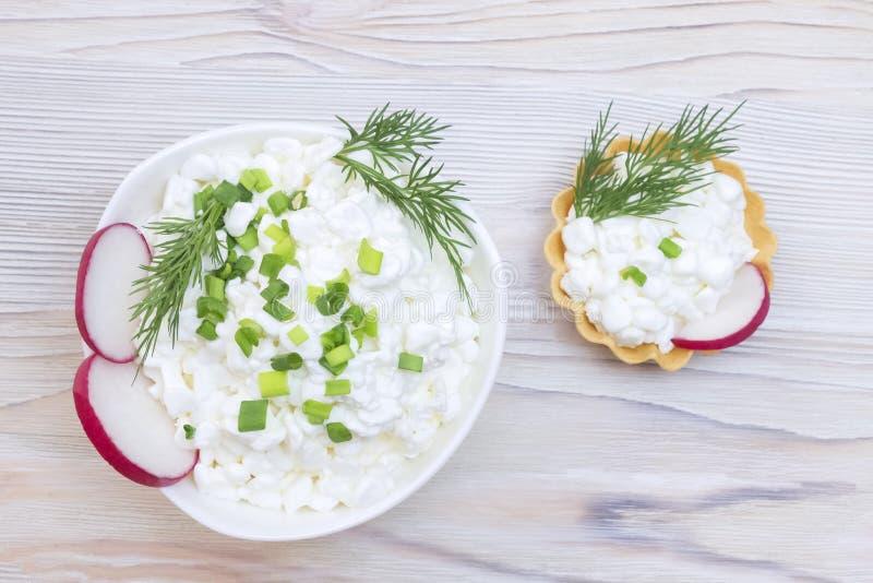 Φρέσκο φυσικό τυρί εξοχικών σπιτιών σε ένα άσπρο κεραμικό κύπελλο στον αγροτικό εκλεκτής ποιότητας ξύλινο πίνακα Πράσινος άνηθος  στοκ εικόνες