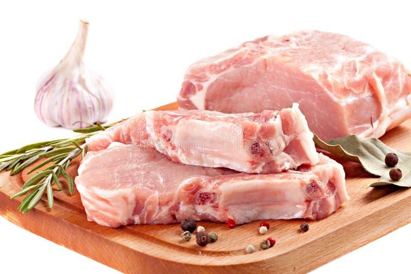 Φρέσκο χοιρινό κρέας σειρών με το δεντρολίβανο και καρυκεύματα στον ξύλινο πίνακα στοκ φωτογραφία