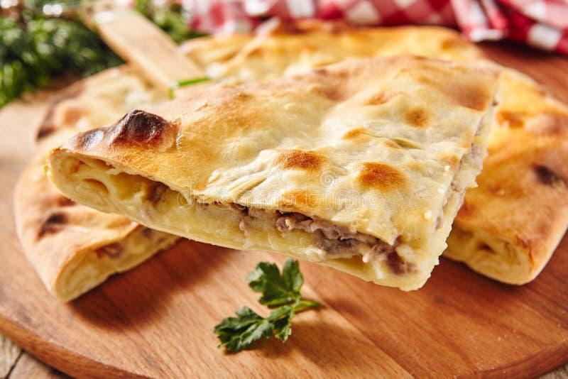 Φρέσκο ψημένο κομμάτι της πίτας που γεμίζεται με το σολομό, την πατάτα και το τυρί στοκ φωτογραφία