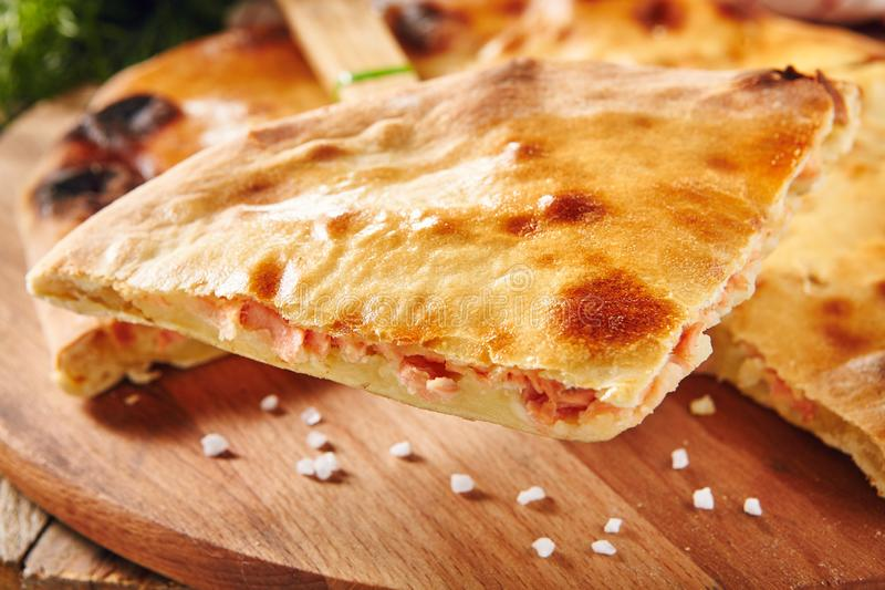 Φρέσκο ψημένο κομμάτι της πίτας που γεμίζεται με το σολομό, την πατάτα και το τυρί στοκ εικόνα με δικαίωμα ελεύθερης χρήσης