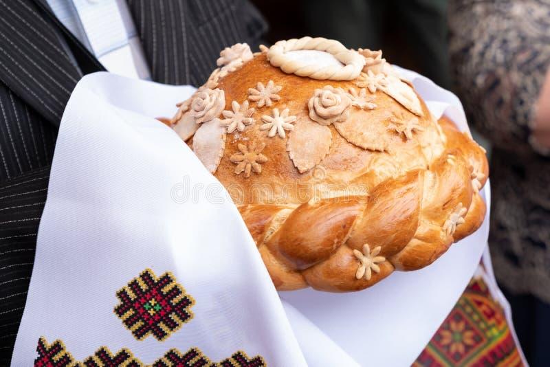 φρέσκο ψωμί με το άλας που κρατά στα χέρια σε μια άσπρη κεντημένη πετσέτα Ρωσικές γαμήλιες παραδόσεις Εύγευστη πίτα στοκ εικόνα
