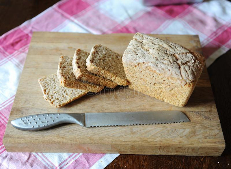 Φρέσκο ψωμί σε ένα ένζυμο σίκαλης χωρίς ζύμη που κόβεται σε έναν ξύλινο τέμνοντα πίνακα σε ένα ελεγμένο τραπεζομάντιλο στοκ φωτογραφίες με δικαίωμα ελεύθερης χρήσης