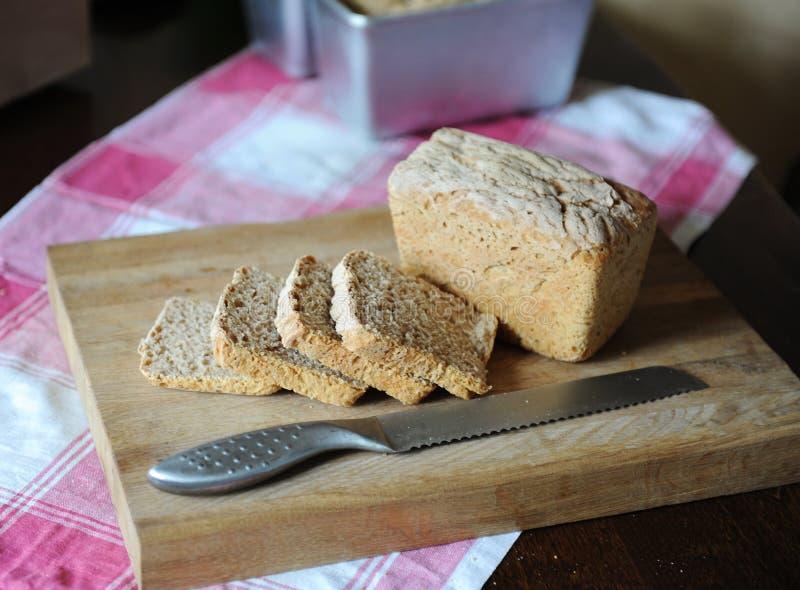 Φρέσκο ψωμί σε ένα ένζυμο σίκαλης χωρίς ζύμη που κόβεται σε έναν ξύλινο τέμνοντα πίνακα σε ένα ελεγμένο τραπεζομάντιλο στοκ εικόνες