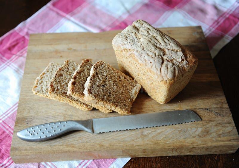 Φρέσκο ψωμί σε ένα ένζυμο σίκαλης χωρίς ζύμη που κόβεται σε έναν ξύλινο τέμνοντα πίνακα σε ένα ελεγμένο τραπεζομάντιλο στοκ φωτογραφία