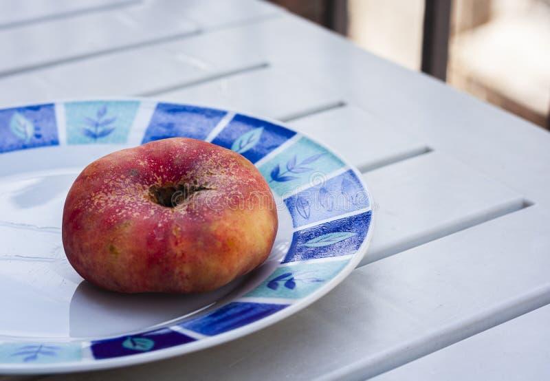 Φρέσκο ώριμο doughnut επίπεδο ροδάκινο περσική προύμνη στο πιάτο στοκ εικόνες