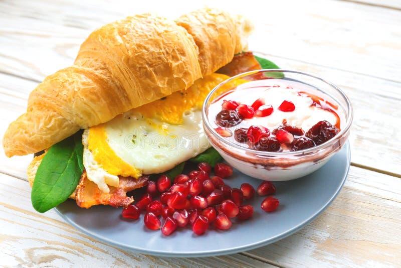 Φρέσκο croissant σάντουιτς, σπιτικό γιαούρτι, ρόδι για το σπάσιμο στοκ φωτογραφία