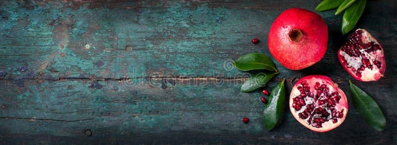 Φρέσκο juicy ρόδι - σύνολο και περικοπή, με τα φύλλα σε ένα ξύλινο εκλεκτής ποιότητας υπόβαθρο, τοπ άποψη, οριζόντια στοκ εικόνα με δικαίωμα ελεύθερης χρήσης