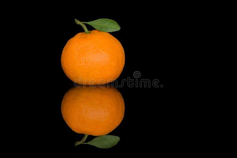 Φρέσκο tangerine με ένα μικρό φύλλο σε ένα μαύρο υπόβαθρο στοκ εικόνα με δικαίωμα ελεύθερης χρήσης