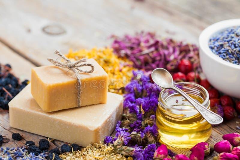 Φραγμοί των σπιτικών σαπουνιών, του μελιού ή του ελαίου και των σωρών της θεραπείας των χορταριών στοκ φωτογραφία με δικαίωμα ελεύθερης χρήσης