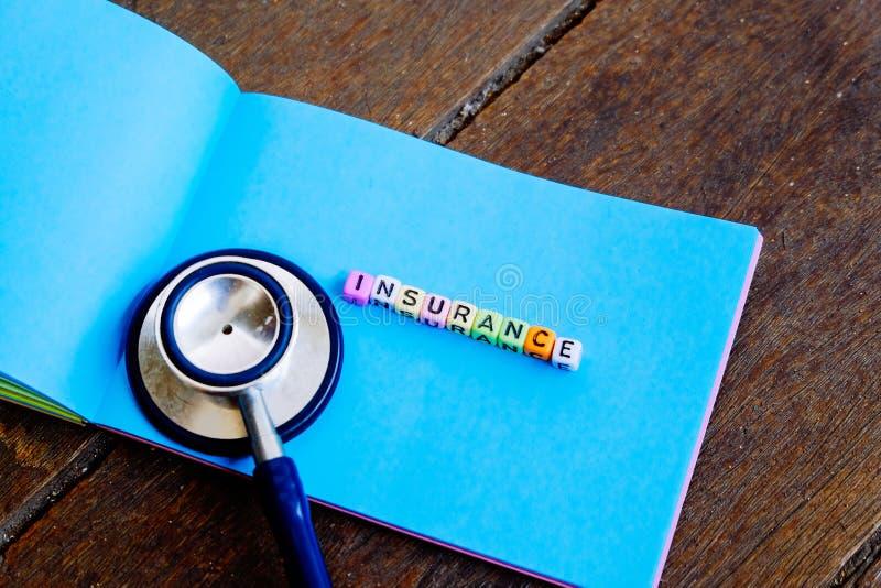 Φραγμός ΑΣΦΑΛΙΣΤΙΚΗΣ λέξης στο σημειωματάριο και στηθοσκόπιο πέρα από το ξύλινο υπόβαθρο στοκ εικόνες