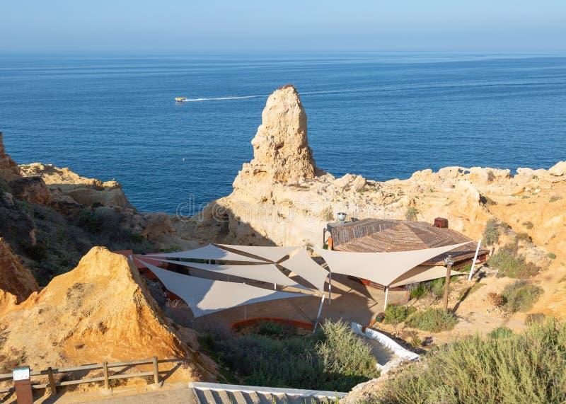 Φραγμός και εστιατόριο Boneca ένα δημοφιλές εστιατόριο σχαρών που τίθεται στους απότομους βράχους κοντά σε Carvoeiro στην Πορτογα στοκ φωτογραφία με δικαίωμα ελεύθερης χρήσης