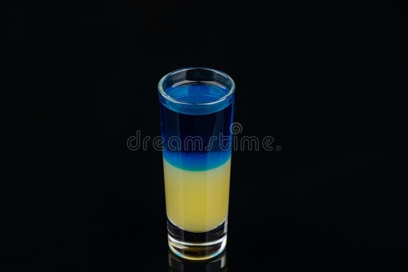 Φραγμός οινοπνεύματος, γυαλί κοκτέιλ στο μαύρο υπόβαθρο, πυροβοληθε'ν μπλε κίτρινο χρώμα κοκτέιλ στοκ εικόνες