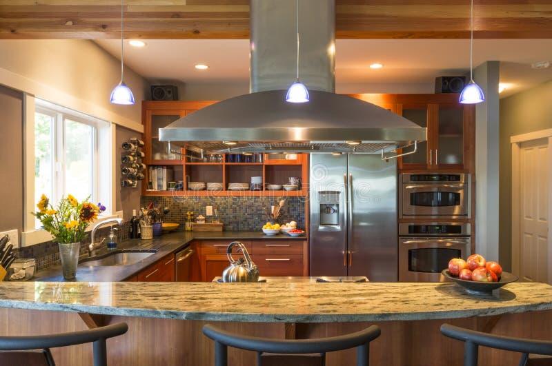 Φραγμός προγευμάτων στο σύγχρονο εσωτερικό εγχώριων κουζινών upscale με countertops γρανίτη, την κουκούλα διεξόδων και το φωτισμό στοκ φωτογραφία με δικαίωμα ελεύθερης χρήσης