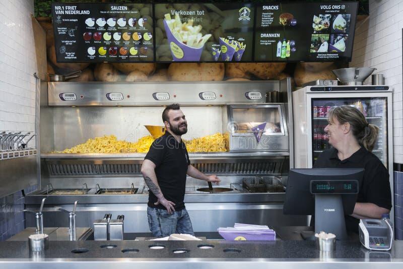 Φραγμός πρόχειρων φαγητών ειδικευμένος στις τηγανιτές πατάτες και προσωπικό που έχει τη διασκέδαση στοκ εικόνες