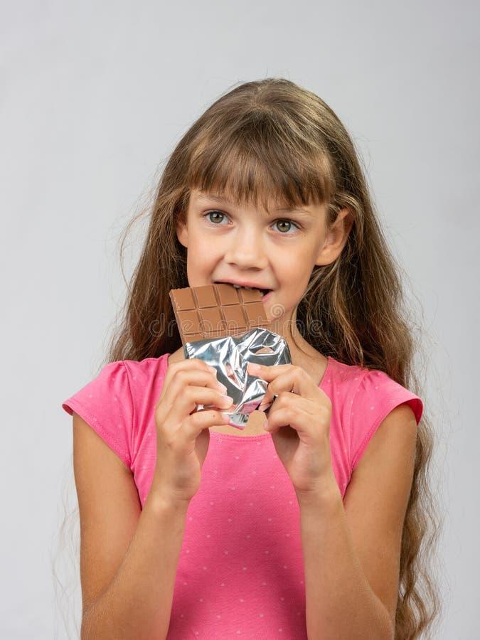 Φραγμός σοκολάτας δαγκωμάτων κοριτσιών εφήβων και αριστερός στοκ φωτογραφία