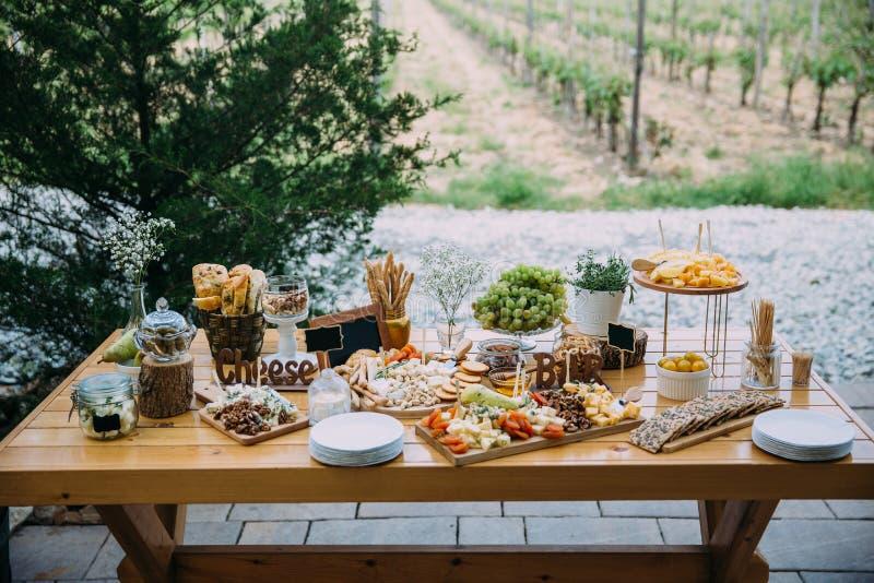 Φραγμός τυριών διάφορων ειδών τυριού, πρόχειρα φαγητά, μέλι, καρύδια που διακοσμούνται στον ξύλινο πίνακα στη δεξίωση γάμου Έννοι στοκ εικόνα