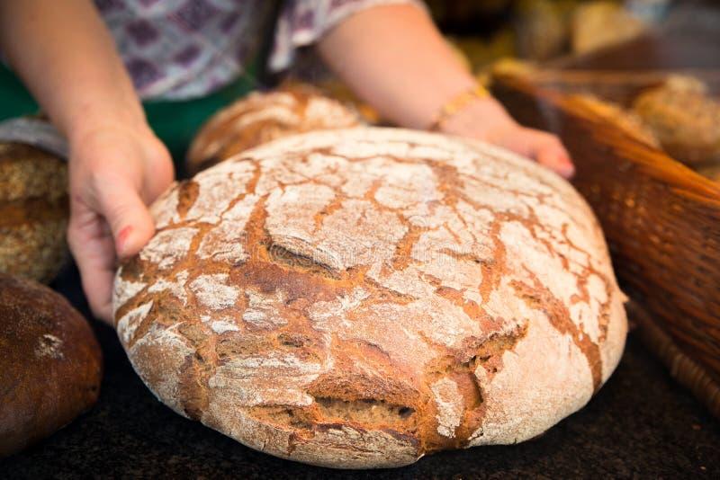 Φραντζόλα επιδείξεων Baker του φρέσκου φλοιώδους ψωμιού στοκ εικόνα