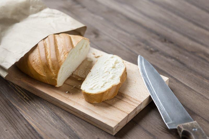 Φραντζόλα, κομμάτι περικοπών του ψωμιού στον τέμνοντα πίνακα, μαχαίρι στο ξύλινο υπόβαθρο στοκ φωτογραφία με δικαίωμα ελεύθερης χρήσης