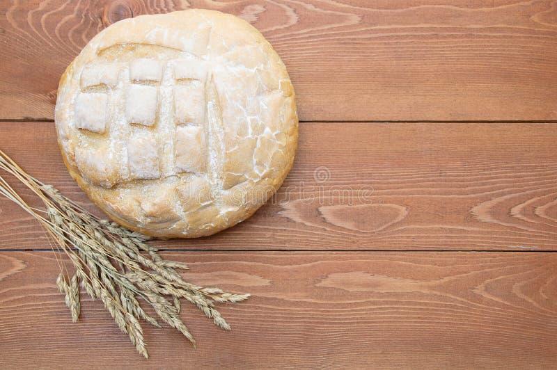 Φραντζόλα του ψωμιού σε ένα καφετί ξύλινο υπόβαθρο Κινηματογράφηση σε πρώτο πλάνο στοκ εικόνες
