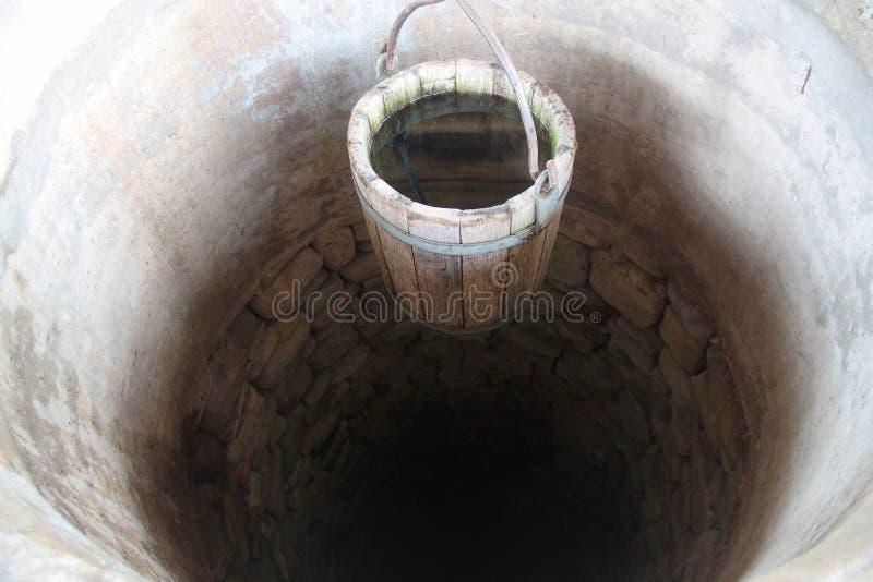 Φρεάτιο νερού των πετρών με τον ξύλινο κάδο στοκ φωτογραφία
