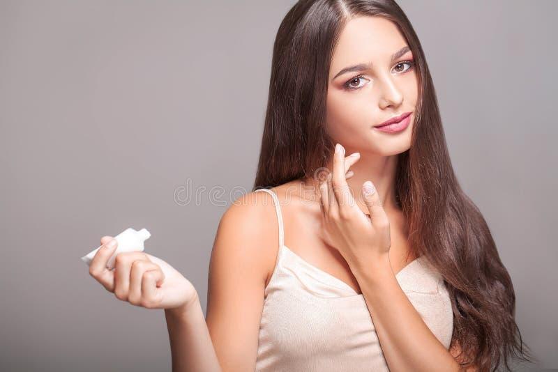 Φροντίδα δέρματος προσώπου γυναικών Πορτρέτο ελκυστικού νέου θηλυκού Applyi στοκ εικόνες