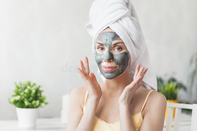 Φροντίδα δέρματος προσώπου Ελκυστική νέα γυναίκα που τυλίγεται στην πετσέτα λουτρών, που εφαρμόζει τη μάσκα λάσπης αργίλου στο πρ στοκ φωτογραφίες με δικαίωμα ελεύθερης χρήσης