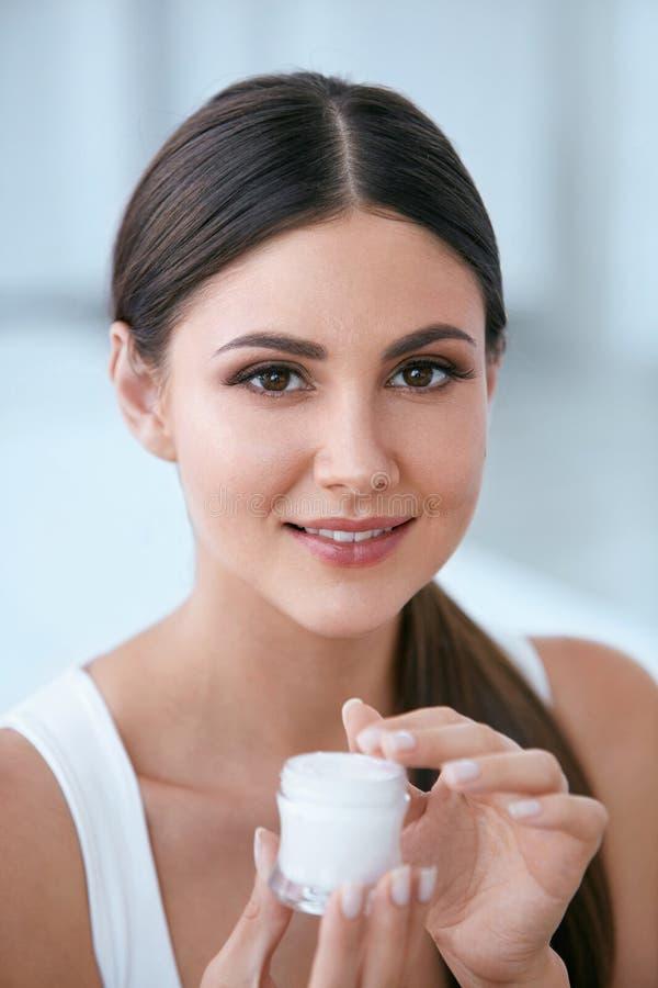 Φροντίδα δέρματος προσώπου Όμορφη γυναίκα με την του προσώπου κρέμα Καλλυντικά στοκ φωτογραφία με δικαίωμα ελεύθερης χρήσης