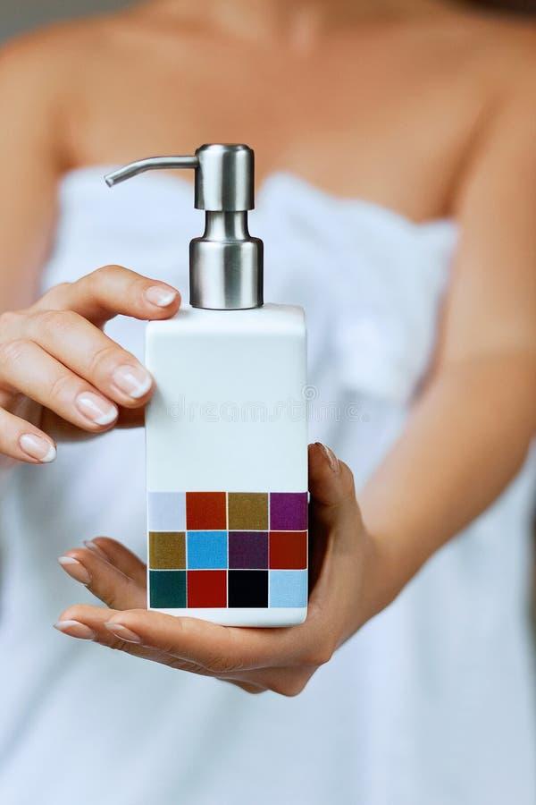 Φροντίδα δέρματος χεριών Κλείστε επάνω του θηλυκού μπουκαλιού κρέμας εκμετάλλευσης χεριών, χέρια γυναικών με τα φυσικά καρφιά μαν στοκ φωτογραφία με δικαίωμα ελεύθερης χρήσης
