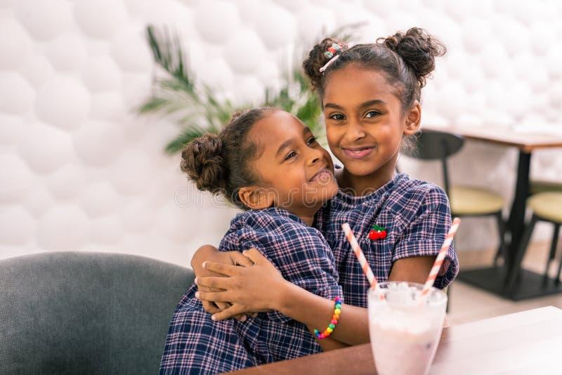 Φροντίζοντας αγαπώντας παλαιότερη αδελφή που αγκαλιάζει τη χαριτωμένη μικρή αδελφή της που φορά το τακτοποιημένο φόρεμα στοκ φωτογραφίες