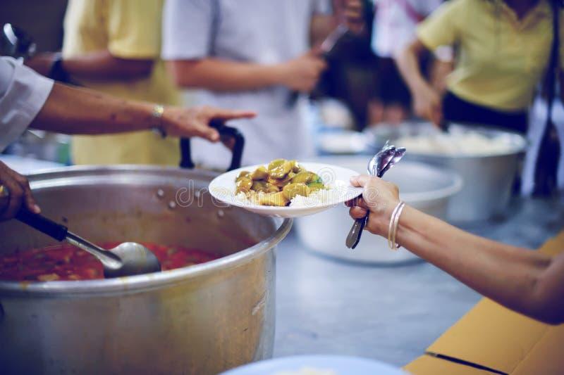 Φροντίζοντας για τα συντροφικά ανθρώπινα οντα στην κοινωνία με το δόσιμο των τροφίμων, που δίνουν χωρίς ελπίδα: Η έννοια της φτωχ στοκ φωτογραφία