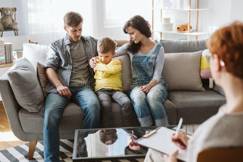 Φροντίζοντας γονείς και συμπεριφεμένος απρεπώς αγόρι κατά τη διάρκεια της συνόδου θεραπείας με το σύμβουλο στοκ φωτογραφία