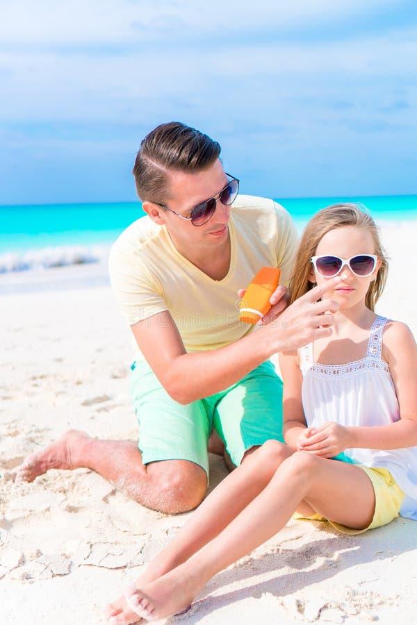 Φροντίζοντας πατέρας που εφαρμόζει την κρέμα ήλιων στη μύτη κορών στην παραλία Η έννοια προστασία από την υπεριώδη ακτινοβολία στοκ φωτογραφία με δικαίωμα ελεύθερης χρήσης
