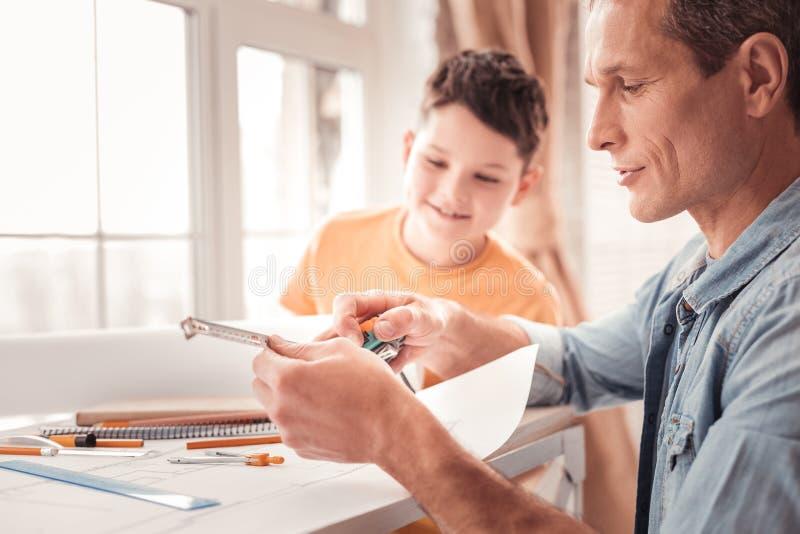 Φροντίζοντας πατέρας που μιλά για τη γεωμετρία με τον επιμελή γιο του στοκ φωτογραφίες με δικαίωμα ελεύθερης χρήσης