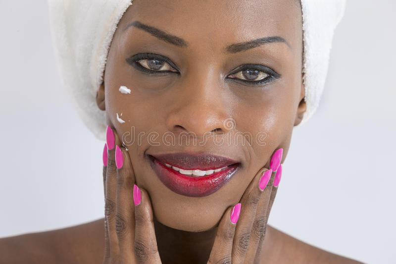 φροντίστε η λήψη δερμάτων τ&eta Πορτρέτο της όμορφης νέας αφροαμερικανίδας γυναίκας που τυλίγεται στην κρέμα διάδοσης πετσετών στ στοκ φωτογραφία με δικαίωμα ελεύθερης χρήσης