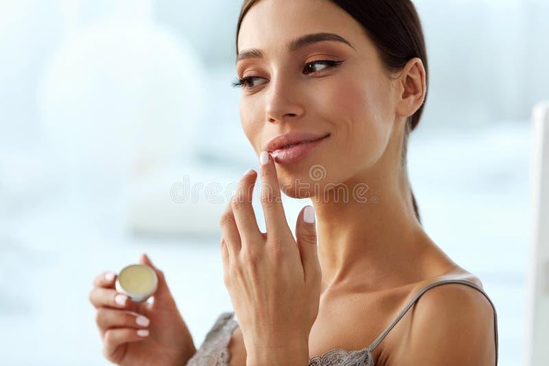 Φροντίδα χειλικού δέρματος Γυναίκα με το πρόσωπο ομορφιάς που εφαρμόζει το χειλικό βάλσαμο επάνω στοκ εικόνα