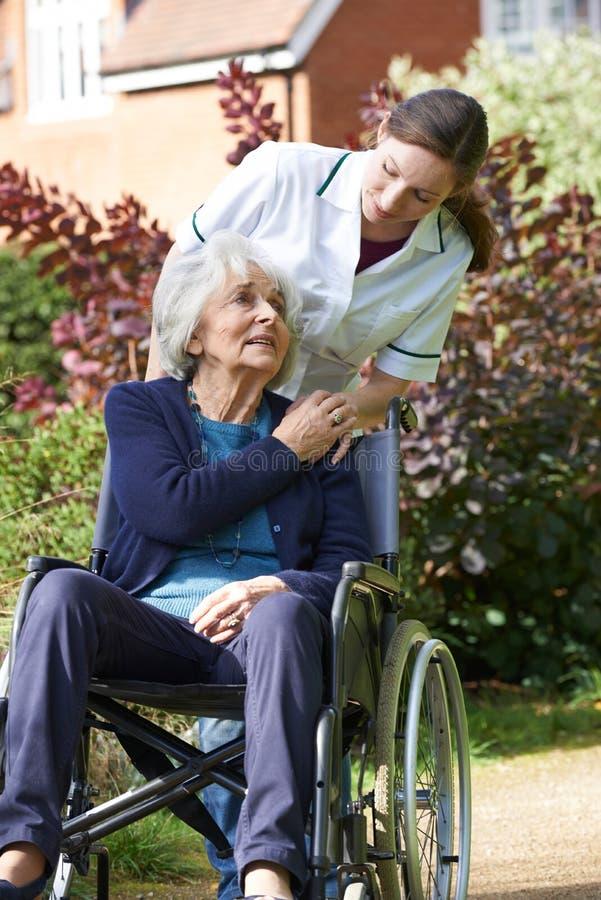 Φροντιστής που ωθεί την ανώτερη γυναίκα στην αναπηρική καρέκλα στοκ εικόνες