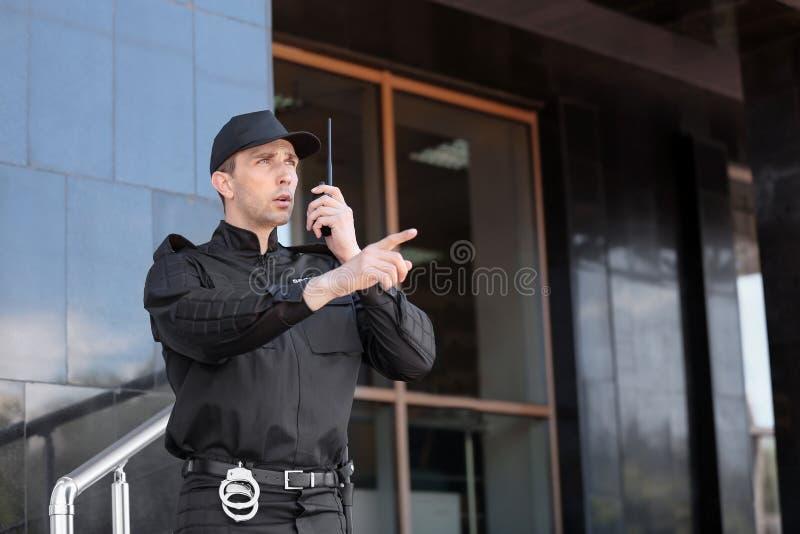 Φρουρά ασφάλειας που χρησιμοποιεί τη φορητή ραδιο συσκευή αποστολής σημάτων υπαίθρια στοκ εικόνες