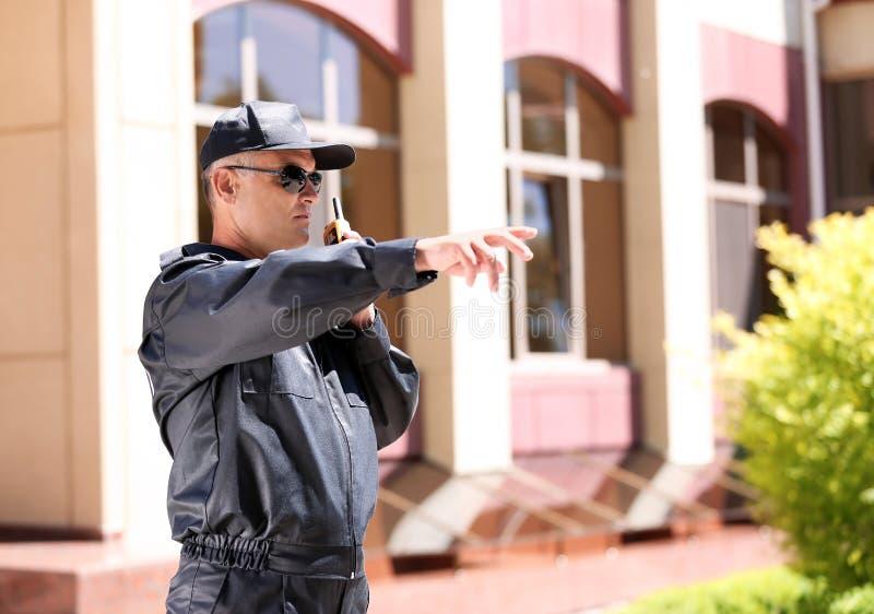 Φρουρά ασφάλειας που χρησιμοποιεί τη φορητή ραδιο συσκευή αποστολής σημάτων υπαίθρια στοκ φωτογραφίες