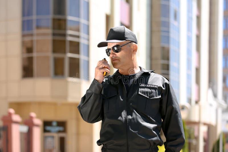 Φρουρά ασφάλειας που χρησιμοποιεί τη φορητή ραδιο συσκευή αποστολής σημάτων υπαίθρια στοκ εικόνα με δικαίωμα ελεύθερης χρήσης
