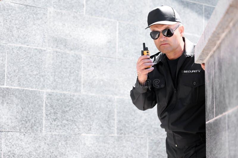 Φρουρά ασφάλειας που χρησιμοποιεί τη φορητή ραδιο συσκευή αποστολής σημάτων υπαίθρια στοκ φωτογραφία