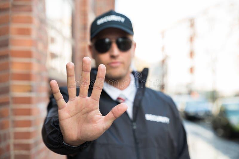 Φρουρά ασφάλειας που κάνει τη στάση να υπογράψει στοκ φωτογραφία