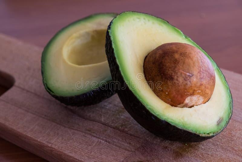Φρούτα αβοκάντο που κόβονται στο μισό στον ξύλινο τέμνοντα πίνακα στοκ φωτογραφία με δικαίωμα ελεύθερης χρήσης